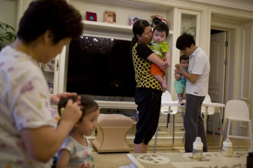 A nanny holds a child of Tony Jiang at his house in Shanghai